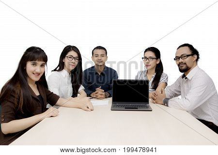 Group of multiracial employees smiling at the camera with laptop computer on the table isolated on white background