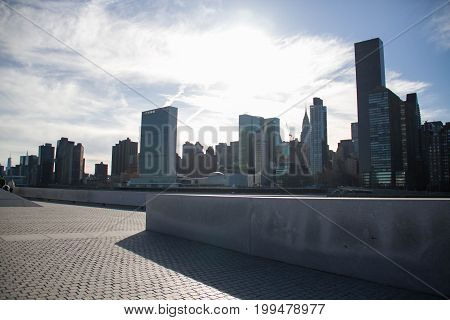 Walkway at Roosevelt island park and Buildings in Manhattan under the shade