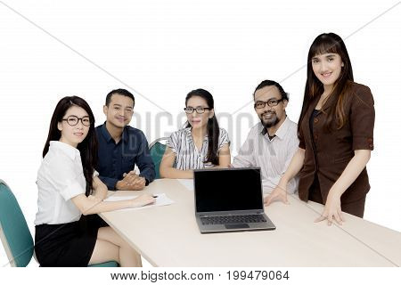 Group of multiracial workers smiling at the camera with a laptop computer on desk isolated on white background