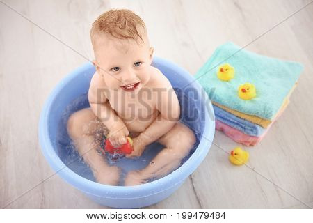 Little baby boy washing in bath basin at home