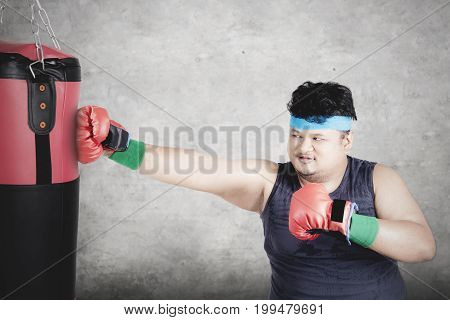 Diet concept. Portrait of a young overweight person doing exercise by punching a boxing sack while wearing sportswear