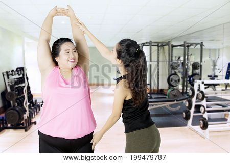 Obese woman doing exercise with her personal trainer in the fitness center