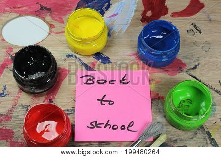 Sign ,,Back to school` on paint pallet with paint tools/This is notice ,,Back to school` on paint pallet with paint tools.