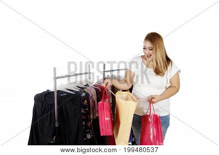 Happy obese woman looking at her shopping bags with clothes hanger on the background