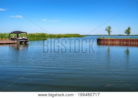 Summer landscape of river with cane growing in it and small boat