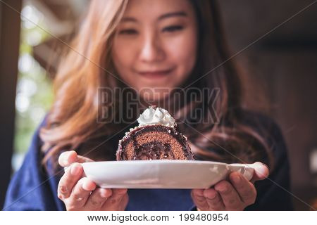 A beautiful asian woman holding chocolate cake roll and whipped cream with feeling happy and good lifestyle in the modern loft cafe