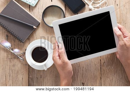 hand business man holding and use tablet on wooden office desk and business objects