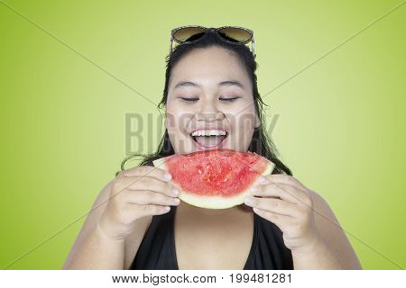 Overweight woman eating a slice of fresh watermelon with green screen