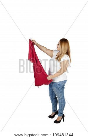 Full length of a young overweight woman holding a red dress to try in the studio isolated on white background