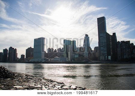 East river and Manhattan next to rock shore at Roosevelt island
