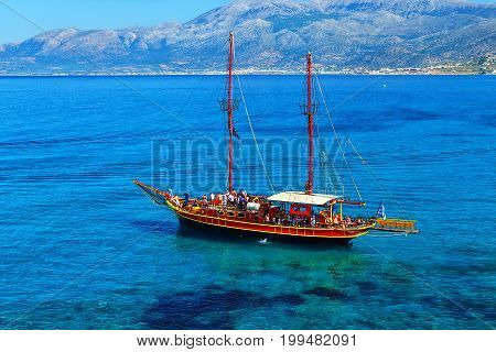 ship like pirate schooners with two masts for sails near the rocks of the coast of Crete