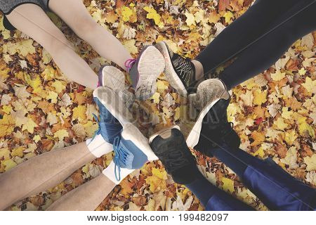Top view of friends make foot circle with their legs and different shoes on autumn leaves at the park