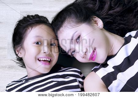 Image of pretty woman with her daughter smiling at the camera while taking a picture together