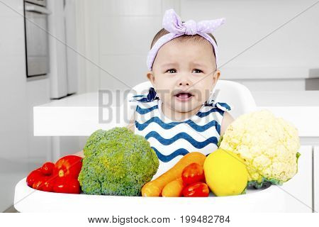 Cute baby looks sad while sitting on the baby chair with fresh vegetables in the kitchen