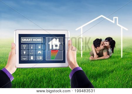 Hands holding a digital tablet with applications icon of smart home controller on the screen shot with young couple lying on grass under a smart home symbol