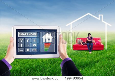 Applications of smart house controller on the tablet screen with young woman and her children using gadget on sofa at field under a house symbol