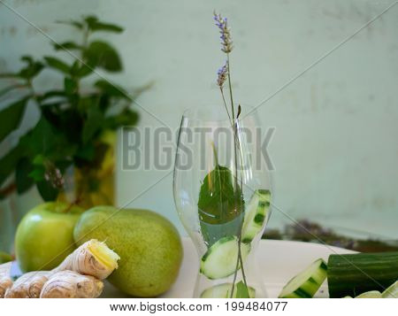 Making Citrus Cucumber detox water with apple, pear, ginger, mint, lavender and sliced lime ingredients healthy and detox water drink on wooden table with light blue background