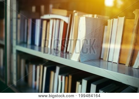 Books on library shelf through window selective focus