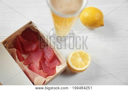 Cardboard box with delicious tuna and glass of beer on wooden table