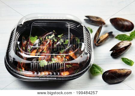 Plastic container with delicious mussels in tomato sauce on wooden table
