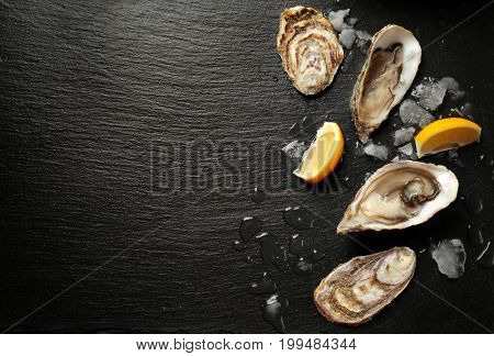 Delicious oysters with slices of lemon and ice cubes on dark table