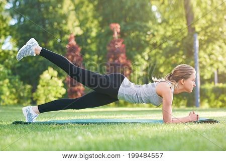 Shot of a young fitness woman working out outdoors at the park doing plank exercise lifting her leg in the air buttocks workout fitness energy motivation athletics activity concept.