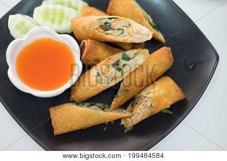 Dim sum spring rolls with sauce on black dish