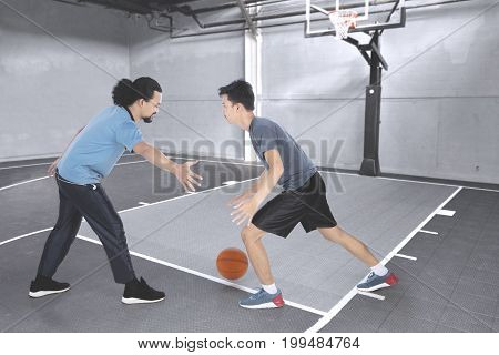 Photo of two young men playing basketball together while doing a friendly match in the basketball court
