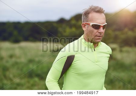 Middle-aged sporty man wearing sunglasses jogging in the countryside though grassland in a close up upper body view with copy space