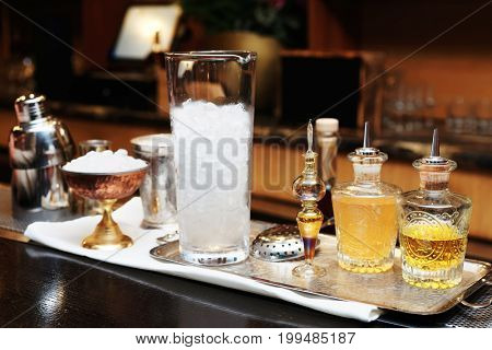 Bitters, infusions and mixing glass with ice on bar counter, toned image