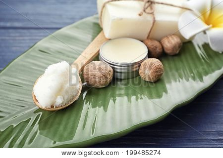 Different cosmetic products with shea butter on plate, closeup