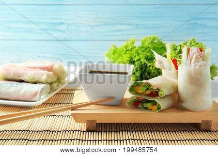 Tasty spring rolls on wooden board