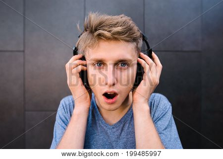 A funny young man with astonished face listens to music in headphones against a background of gray wall. Emotional teenager gets pleasure from music