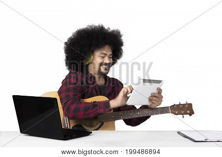 Young musician using a digital tablet with laptop and clipboard on the table isolated on white background