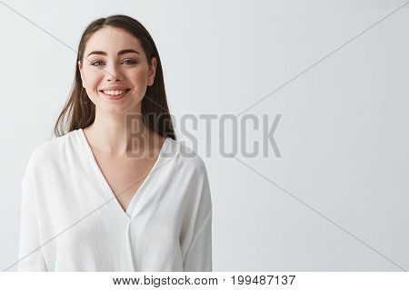 Portrait of happy beautiful young businesswoman smiling looking at camera over white background. Copy space.