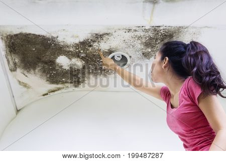 Side view of a young woman pointing at roof damage caused by water leaks