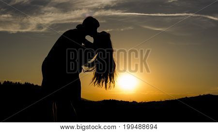 The silhouette of kissing couple during sunset. The boy is holding the girl in his arms.