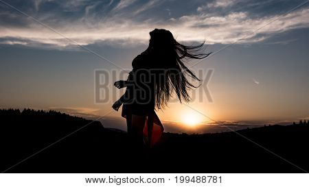 The silhouette of young girl with long hair and dress during sunset. Happy girl . She is laughting. Her hear are waving in the air.