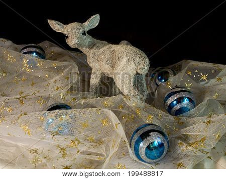 White fawn in the silk with gold stars and blue and silver Christmas balls on the black background. Christmas decoration. Winter time.