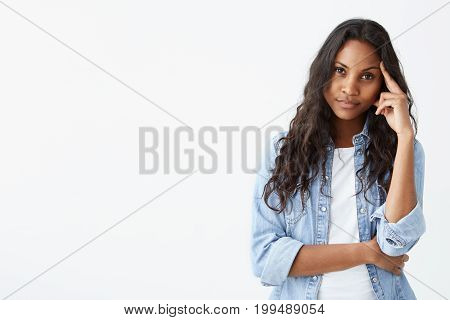 Human emotions, feelings, reaction and attitude. Attractive young dark-skinned woman in denim with long wavy hair squeezing eyes and keeping hand on temple in dissatisfaction and suspicion, feeling sceptical about something.