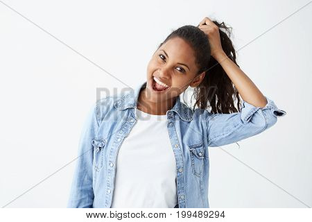Human face expressions and emotions. Portrait of young African-American brunette woman in light-blue denim shirt having fun, holding her hair with hand, with mouth wide open. Cheerful and joyful female.