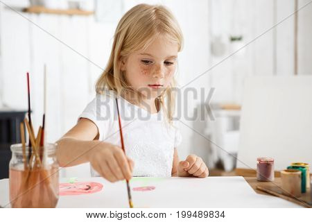 Close up portrait of little white-skinned girl with blonde hair and freckles focused on painting picture for her parents. Blond baby sitting at the desk with brush in her hand.