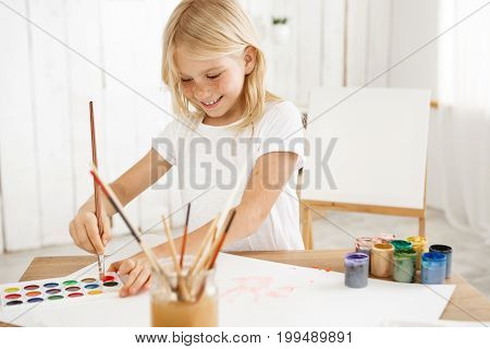 Smiling, inspired girl with blonde hair and freckles joyfully deeping brush into red paint, having new idea for a picture. Eight-year-old charming kid captured by inspiration.
