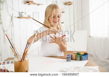 Beautiful, creative and busy little blonde girl in white t-shirt drawing on her palm with a brush. Eight-year-old freckled female kid standing behind desk at the art room filled with sunlight. Kids and art concept.