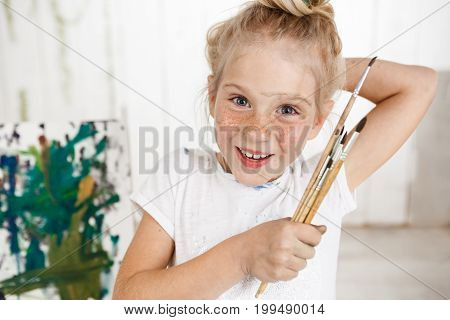 Portrait of angel-like cheerful smiling with teeth child in white morning light in art room, holding in her hand bunch of brushes. Little European girl with blond hair looking happy and joyful showing positive emotions.