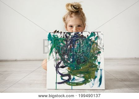 Studio shot of beautiful little blonde girl holding and hiding by the big picture, looking at the camera with cunny and joyful expression. Cute child with hair bun, freckles and blue eyes showing herself up.
