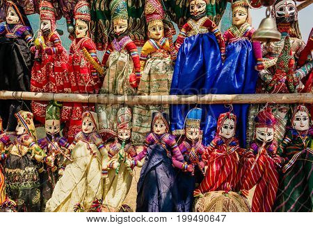 Souvenir toys of traditional Indian market. Faces of funny handmade dolls in old costumes for children in Asia.