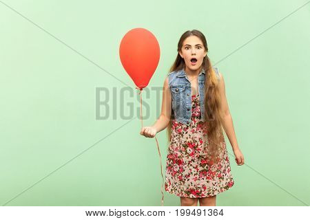Unbelievable! The beautiful blonde teenager is sho?ked looking at camera with red ballon on a light green background. Isolated studio shot