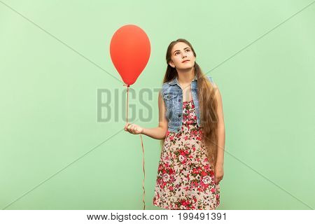 The beautiful blonde teenager dreaming with red ballons on a green background. Isolated studio shot