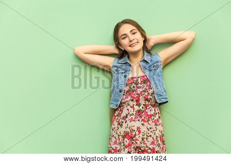 Human positive emotions. The beautiful long haired blonde girl in dress having fun crossed hands onder head front of the light blue wall. Isolated studio shot.